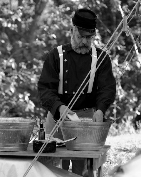 Reenactor Private David Hazen, 6th N.Y. Light Artillery, washes dishes shortly after dinner at Patriots Point, where a small group of Confederate reenactors set up camp, in Mt. Pleasant, South Carolina on Wednesday, April 13, 2011. ..The 150th Anniversary of the Firing on Ft. Sumter was commemorated with lectures, performances, demonstrations, and a living history throughout the area on James Island, Charleston, Mt. Pleasant, and Sullivan's Island during the week from April 8-14, 2011. Photo Copyright 2011 Jason Barnette