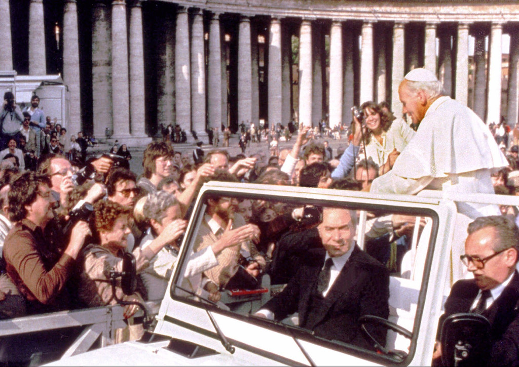 . A hand holding a pistol, left, aims from the crowd at Pope John Paul II in St. Peter\'s Square in Rome in this May 13, 1981 file photo. (AP Photo, File)