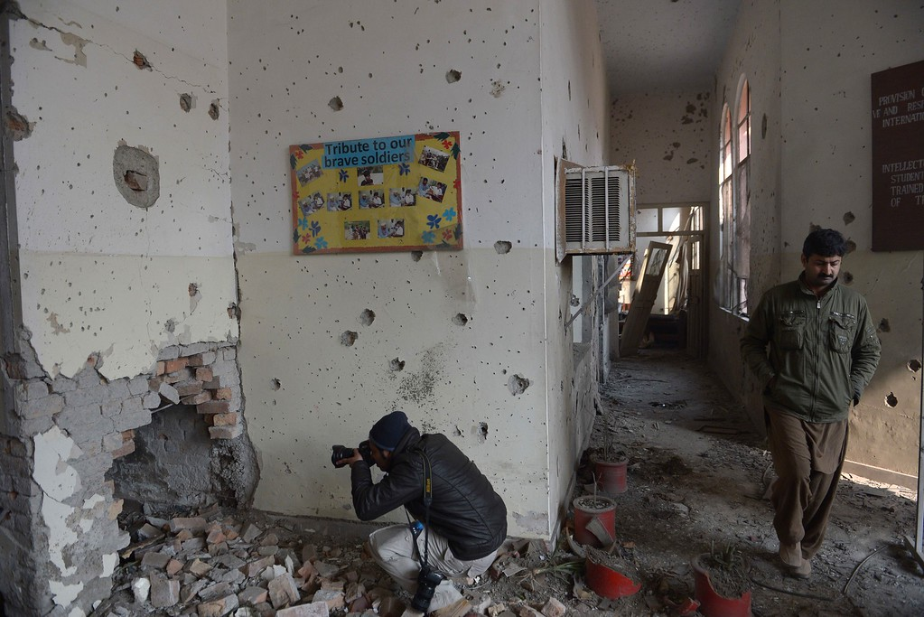 . A Pakistani photographer shoots a bullet-riddeled wall at an army-run school a day after an attack by Taliban militants in Peshawar on December 17, 2014.  Pakistan began three days of mourning on December 17 for the 132 schoolchildren and nine staff killed by the Taliban in the country\'s deadliest ever terror attack as the world united in a chorus of revulsion.  AFP PHOTO / FAROOQ  NAEEM/AFP/Getty Images