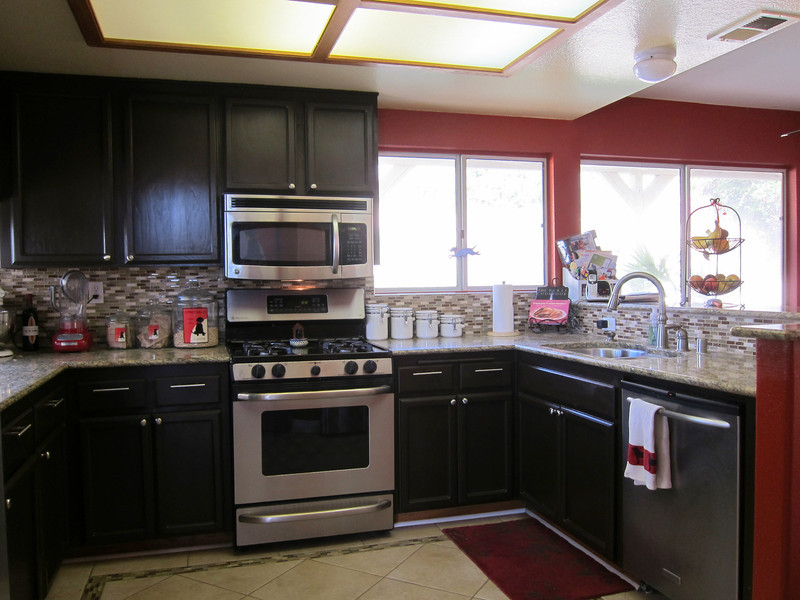 Kitchen has a granite countertop and a glass tile backsplash...