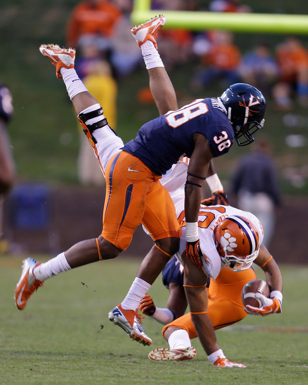 . Clemson tight end Jordan Leggett (16) gets upended after catch as Virginia safety Kelvin Rainey (38) defends during the second half of an NCAA college football game in Charlottesville, Va., Saturday, Nov. 2, 2013.  Clemson won 59-10.  (AP Photo/Steve Helber)