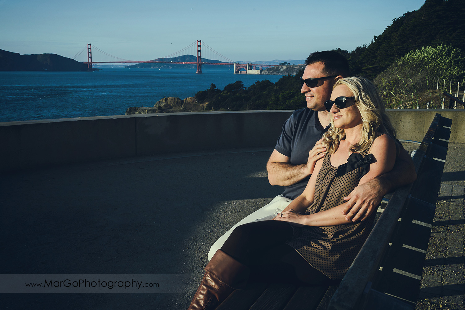 woman in brown tunic and man in navy blue shirt sitting on the bench with Golden Gate Bridge in the background during engagement session at San Francisco Lands End