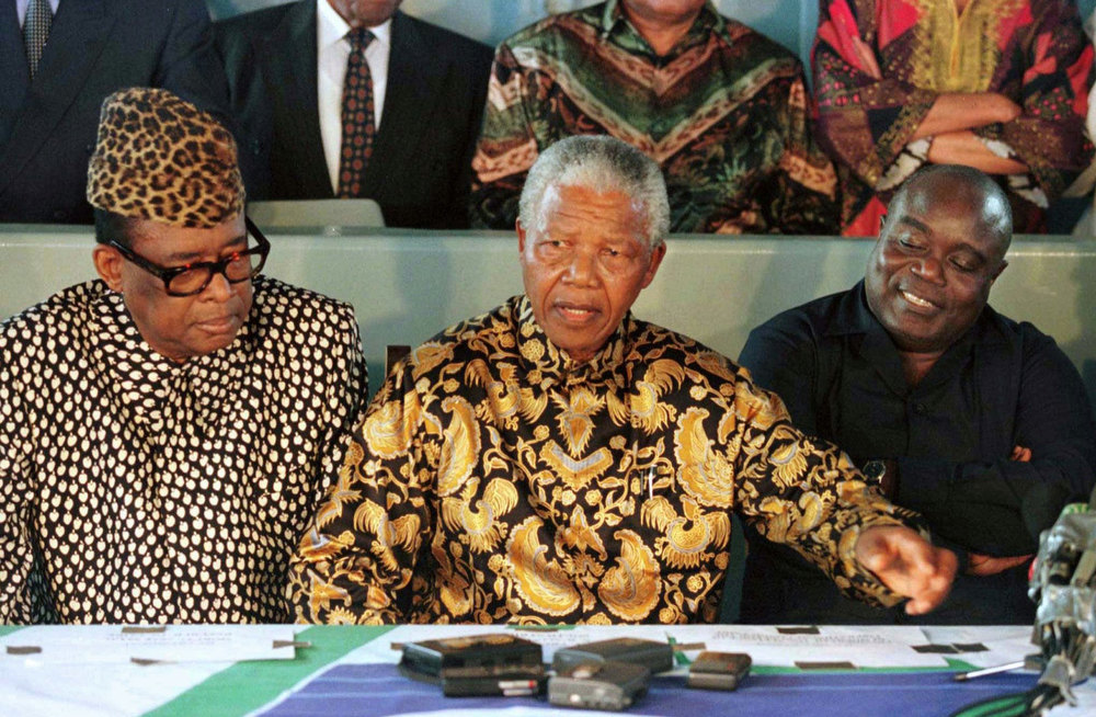 Description of . South African President Nelson Mandela (C) gestures during a press conference with Zairean President Mobutu Sese Seko (L) and rebel leader Laurent-Desire Kabila (R) aboard the SAS Outeniqua in Pointe Noire harbour, Congo Sunday May 4, 1997, after the first face-to-face peace talks between the two rivals. (AP Photo/Philippe Wojazer,POOL)
