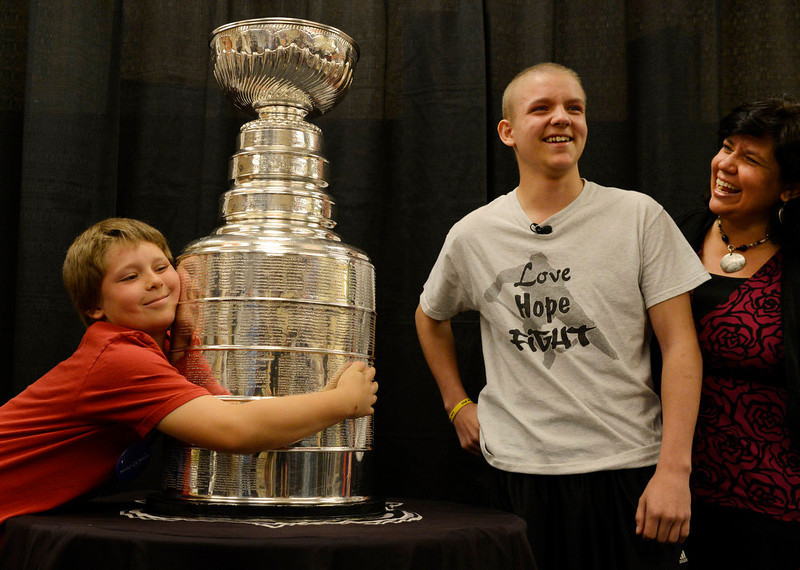 . Hayden Piz, 9, hugs the Stanley Cup while posing for a portrait with his brother, Logan, and their mother, Tammy, at Rocky Mountain Hospital for Children in Denver, CO on May 15, 2013. The hospital, Make-A-Wish, Discover and the National Hockey League teamed up to grant  Logan\'s wish to spend a day with the Stanley Cup and share it with friends, family and supporters. Logan has not played hockey since he was diagnosed with Ewing�s sarcoma in November 2012. (Photo By Craig F. Walker/The Denver Post)
