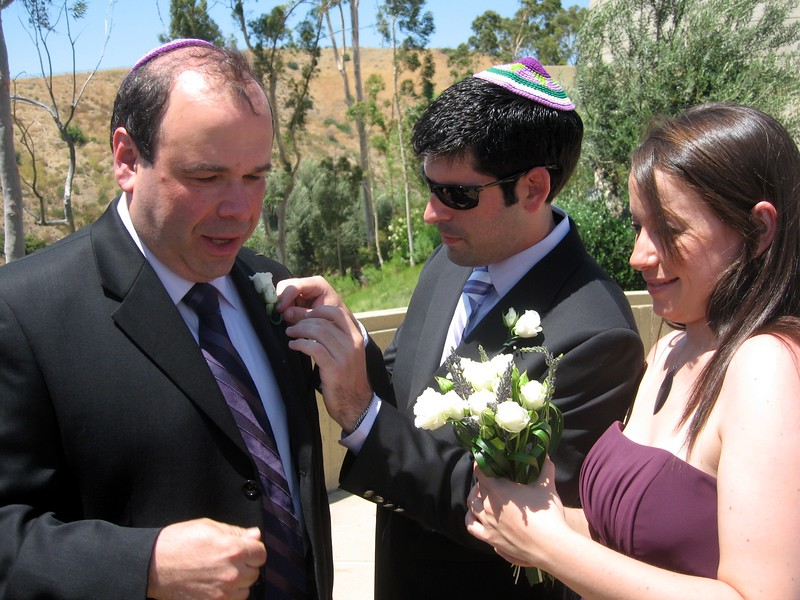 David (brother of the bride) and bridesmaid Rebecca help Gary (father of the bride) with his boutonnière
