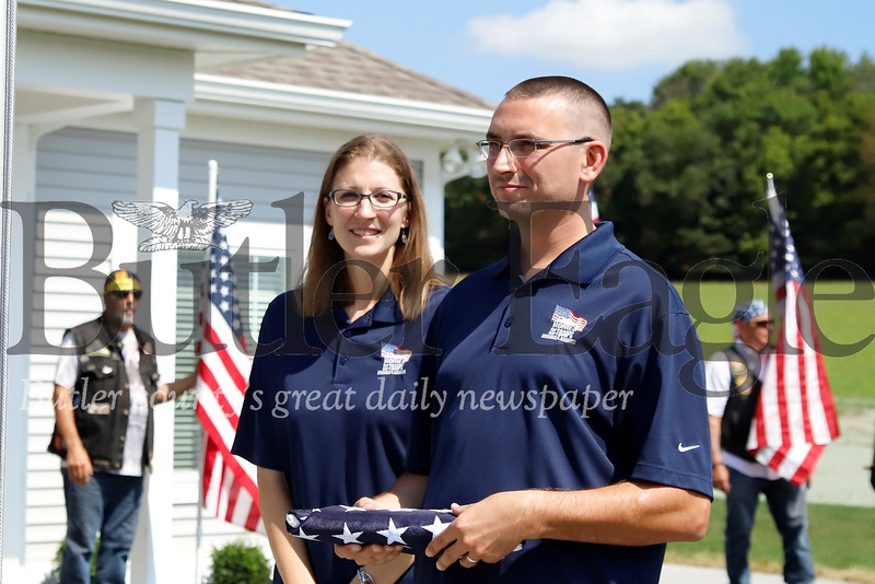 U.S. veteran Justin Hendrickson and his wife Jennie get ready to raise the American flag at their new house as part of a ceremony for Homes for Troups Saturday 08/03/12. Hendrickson lost a leg serving in Iraq and his wife is a brain cancer survivor. Seb Foltz/Butler Eagle