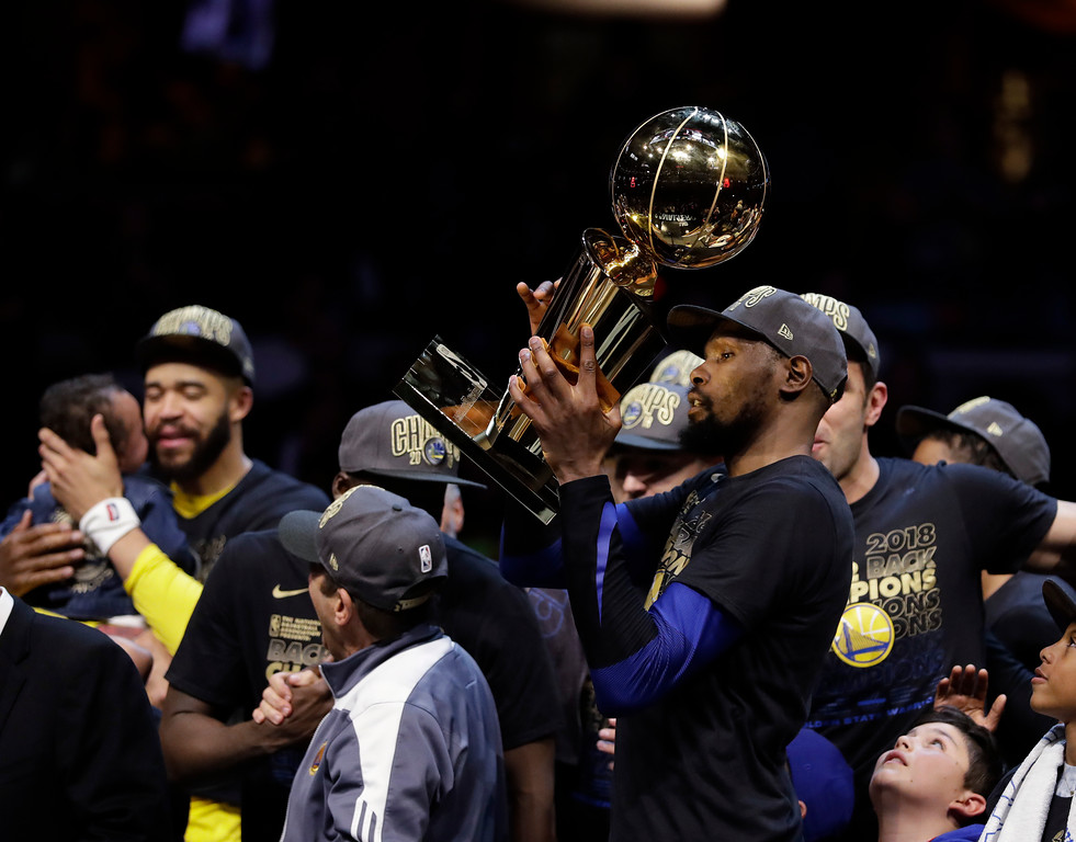 . Golden State Warriors\' Kevin Durant celebrates with the trophy after the Warriors defeated the Cleveland Cavaliers 108-85 in Game 4 of basketball\'s NBA Finals to win the NBA championship, Friday, June 8, 2018, in Cleveland. (AP Photo/Tony Dejak)