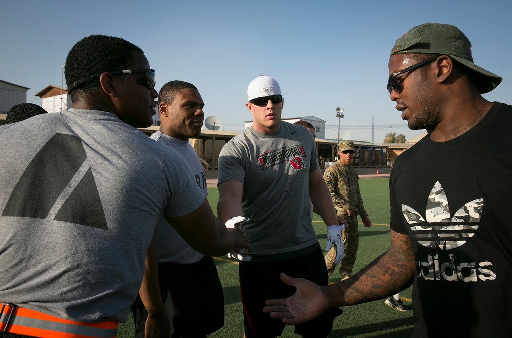 . Houston Texans defensive end J.J. Watt (2nd r) and Denver Broncos linebacker Von Miller (r) shake hands with soldiers stationed in the Middle East following an impromptu touch football game with service members during a stop of their week-long USO/NFL tour March 16, 2013. USO Photo by Fred Greaves