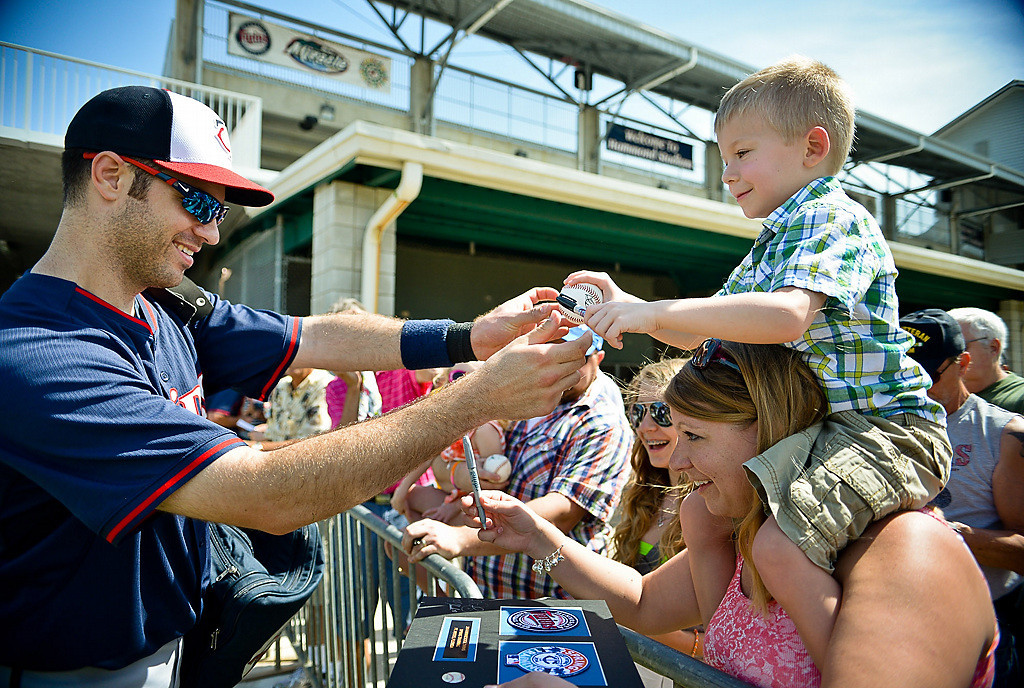 . Twins first baseman Joe Mauer reaches out to five-year-old Jack Klemmensen of Otsego, Minn., who had to perch on his mom Jen\'s shoulders to measure up to Mauer for an autograph in Ft. Myers, Fla. on Sunday, February 23, 2014. (Pioneer Press: Ben Garvin)