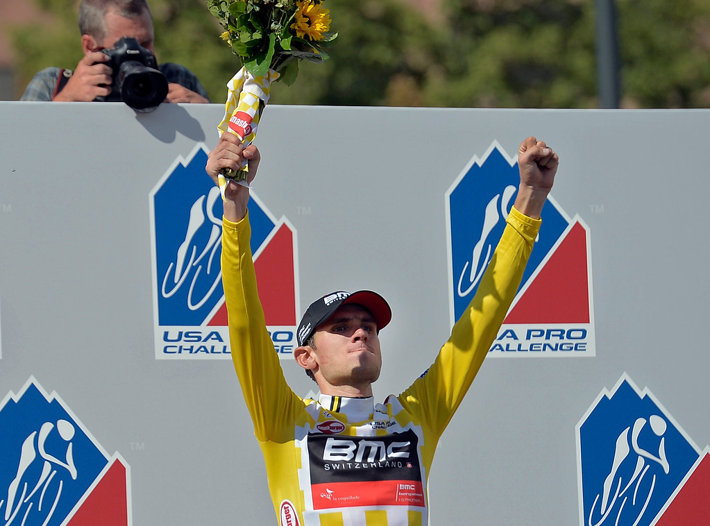 . Aspen\'s Tejay Van Garderen of BMC Racing raises his arms up during ceremonies after winning the 3rd annual Pro Cycle Challenge August 25, 2013 in Denver, Colorado. The final stage took place in downtown Denver winding through the streets and finishing near the state Capitol. (Photo by John Leyba/The Denver Post)