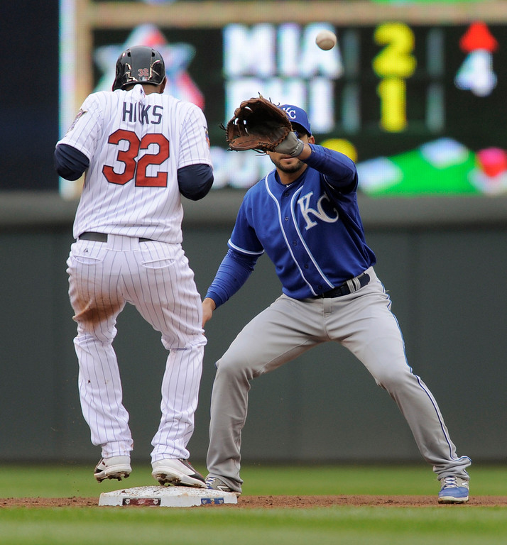 . Minnesota Twinsí Aaron Hicks (32) gets back to second before Kansas City Royals second baseman Omar Infante, right, can make the catch and tag on a pick-off attempt during the third inning. (AP Photo/Tom Olmscheid)