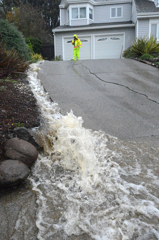 . After a Tiburon Public Works crew clears a drain behind Harn Court on Thursday, Dec. 11, 2014, in Tiburon, Calif, a small river of muddy water runs around the house, down the driveway and into the street. (Frankie Frost/Marin Independent Journal)