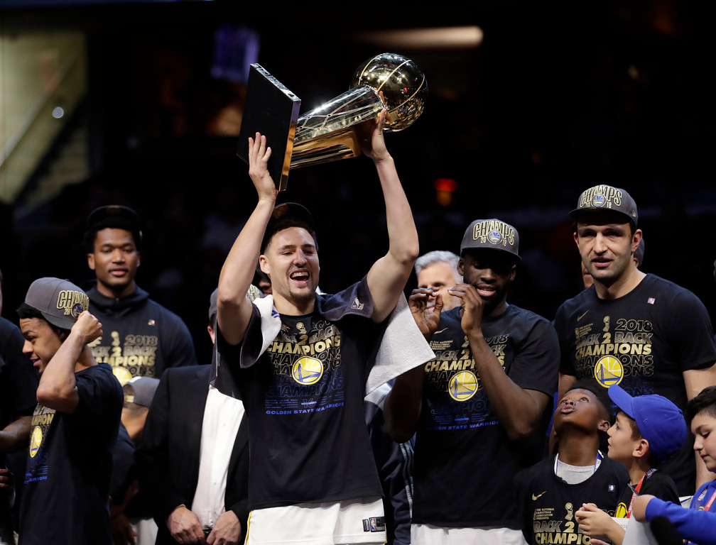 . Golden State Warriors\' Klay Thompson celebrates hols up the trophy after the Warriors defeated the Cleveland Cavaliers 108-85 in Game 4 of basketball\'s NBA Finals to win the NBA championship, Friday, June 8, 2018, in Cleveland. (AP Photo/Tony Dejak)