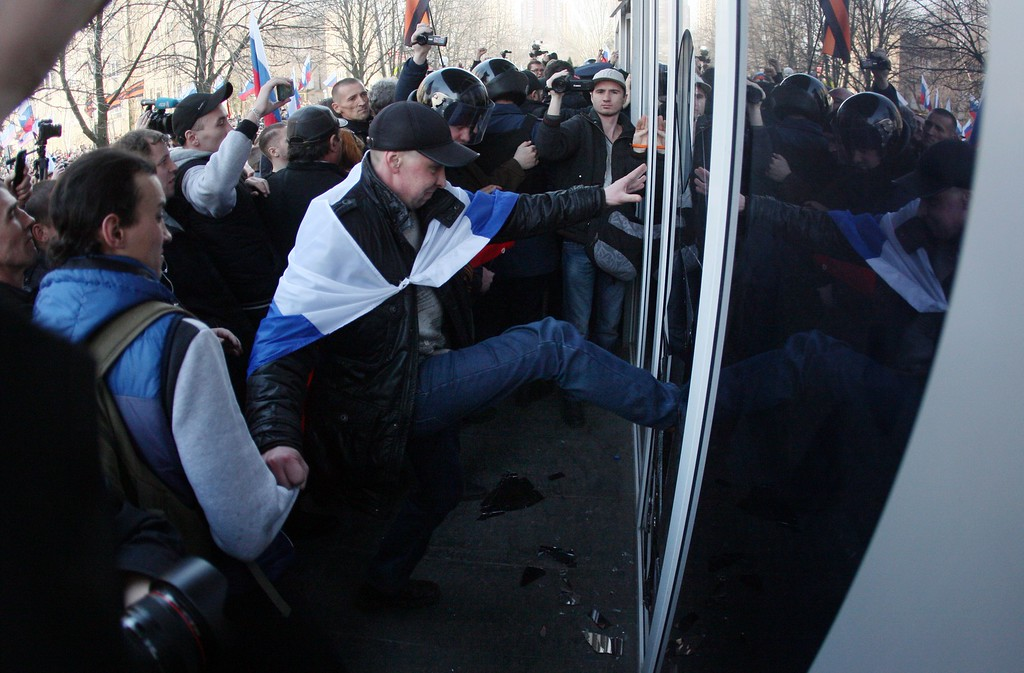 . Pro-Russian activists try to storm into Ukraine\'s Security Service building following a rally in the eastern Ukrainian city of Donetsk on March 15, 2014. Russia vetoed a Western-backed resolution condemning the Crimea referendum at a UN Security Council emergency vote but China abstained, isolating Moscow further on the Ukraine crisis. AFP PHOTO/ALEXANDER KHUDOTEPLY/AFP/Getty Images