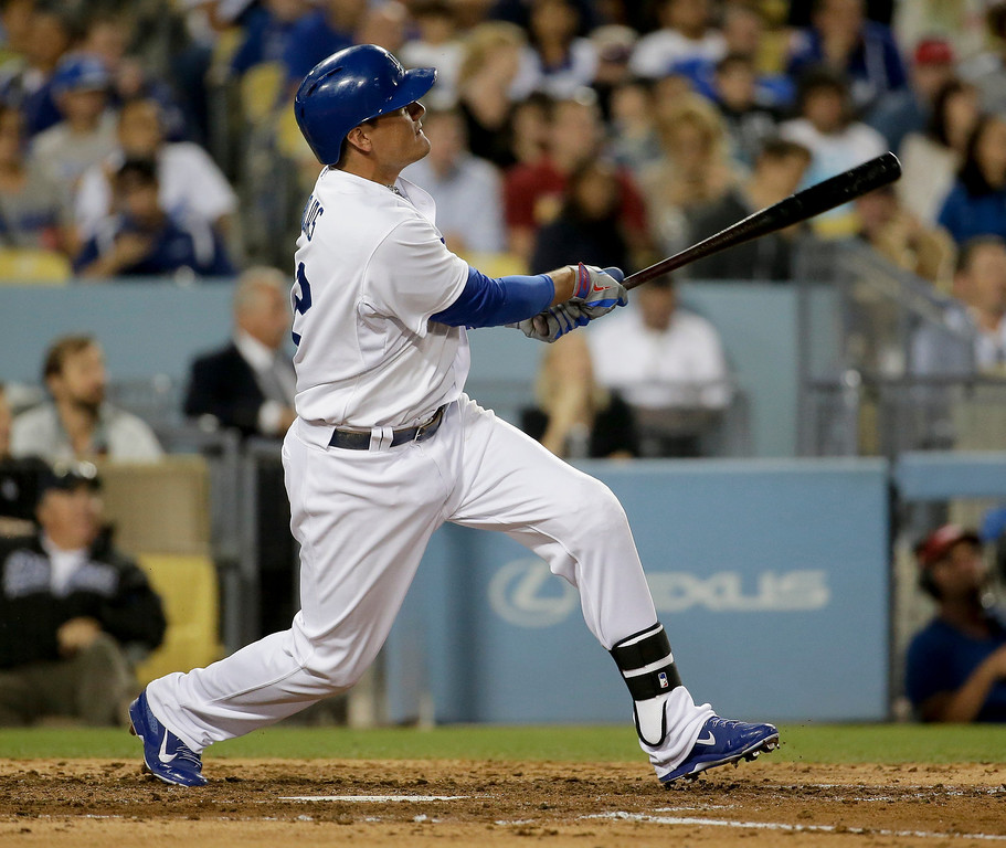 . Los Angeles Dodgers\' Miguel Rojas watches his three-run double against the Colorado Rockies during third inning of a baseball game in Los Angeles, Wednesday, June 18, 2014. (AP Photo/Chris Carlson)