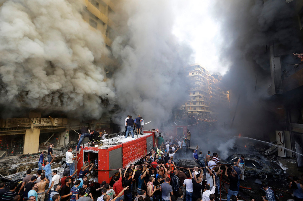 . Lebanese citizens and Hezbollah supporters gather at the scene of a car bomb explosion in southern Beirut, Lebanon, Thursday Aug. 15, 2013. The powerful car bomb ripped through a southern Beirut neighborhood that is a stronghold of the militant group Hezbollah on Thursday, killing at least three people and trapping others in burning buildings, the media said. (AP Photo/Hussein Malla)