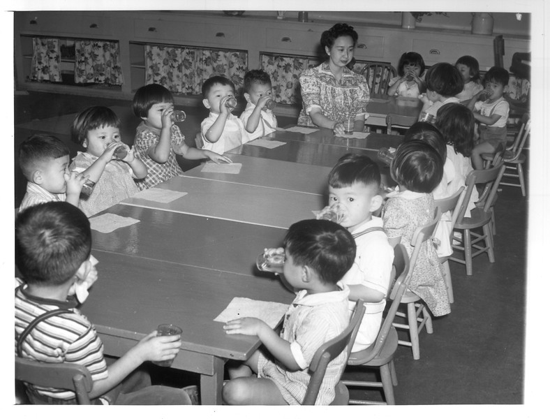 """""""Mrs. F. Kitagawa (Nisei), teacher of a Japanese kindergarten, and her class of three-year-old pupils (Sensei).  The class is drinking its morning tomato juice.""""--caption on photograph"""