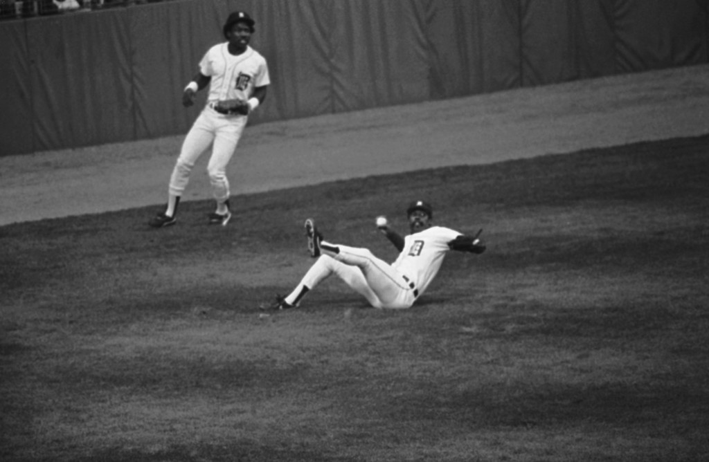 . Detroit left fielder Larry Herndon, center, falls as he throws to stop Garry Templeton at a double in the fourth inning of World Series game five at Tiger Stadium, Oct. 14, 1984, Detroit, Mich. Backing him up is center fielder Chet Lemon, left. (AP Photo/Rob Kozloff)