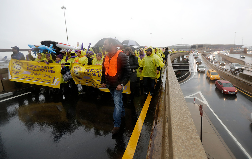 . Service workers asking for $15 minimum wage pay march on a road between terminals at Newark Liberty International Airport, Tuesday, Nov. 29, 2016, in Newark, N.J. The event was part of the National Day of Action to Fight for $15. The campaign seeks higher hourly wages, including for workers at fast-food restaurants and airports. (AP Photo/Julio Cortez)