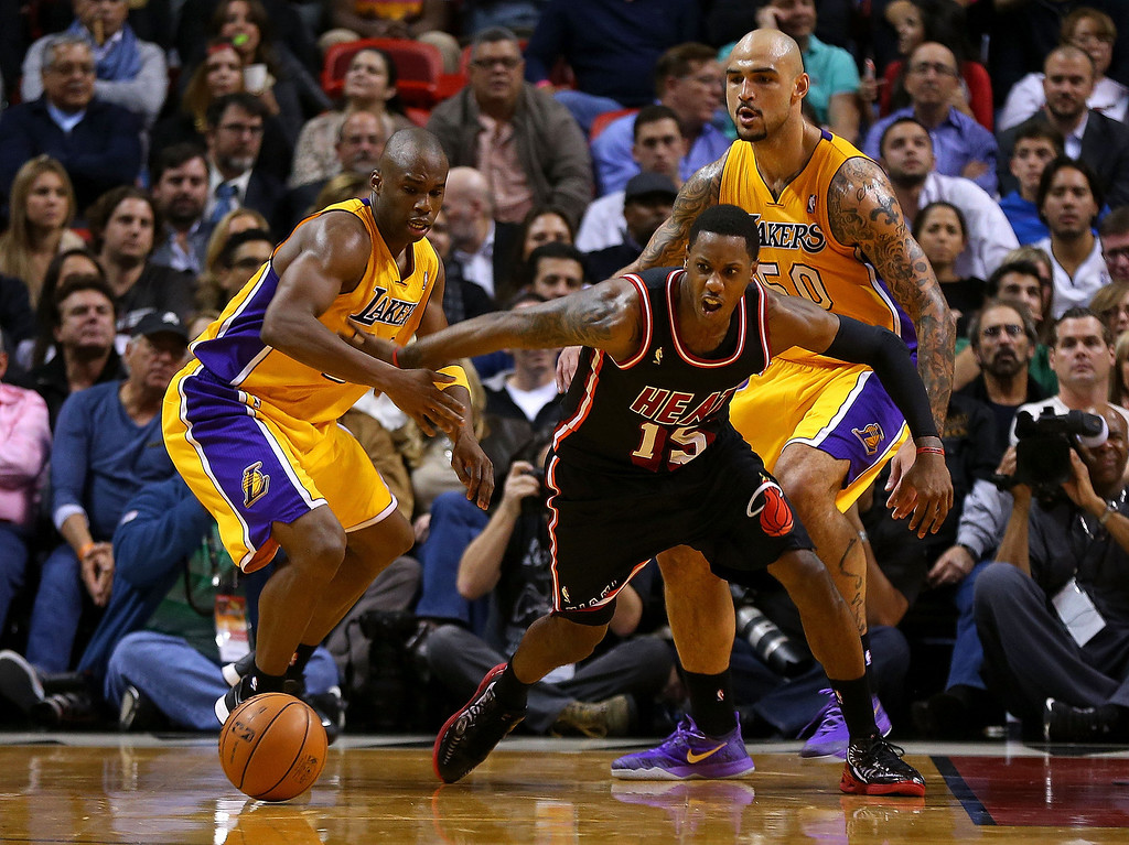 . Mario Chalmers #15 of the Miami Heat and Jodie Meeks #20 of the Los Angeles Lakers go for a loose ball during a game  at American Airlines Arena on January 23, 2014 in Miami, Florida.  (Photo by Mike Ehrmann/Getty Images)