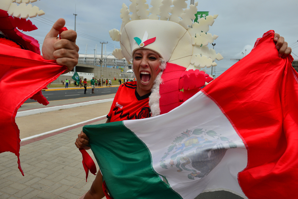 . A Mexican supporter waves her national flag as she stands outside The Castelao Stadium in Fortaleza on June 17, 2014, ahead of the Group A football match between Brazil and Mexico during the 2014 FIFA World Cup.  (YURI CORTEZ/AFP/Getty Images)