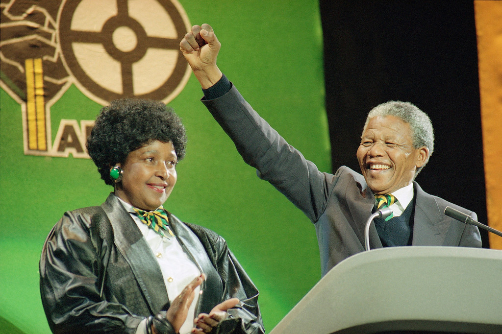. South African anti-apartheid leader Nelson Mandela with his wife Winnie at his side, raises his fist as he acknowledges the cheers of thousands at a rock concert  Monday, April 16, 1990 at London\'s Wembley Stadium. (AP Photo/Martin Cleaver)
