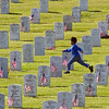 john green/staff5/27/06 smc times news<br /> A cub scout races to put another flag on one of the 116,700 grave sites at the Goldent Gate National Cemetary in San Bruno Saturday morning.