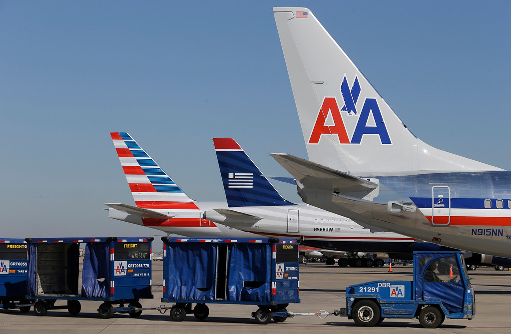 . U.S. Airways and American Airlines planes are shown at gates at DFW International Airport Thursday, Feb. 14, 2013, in Grapevine, Texas. The two airlines will merge forming the world\'s largest airlines.  (AP Photo/LM Otero)