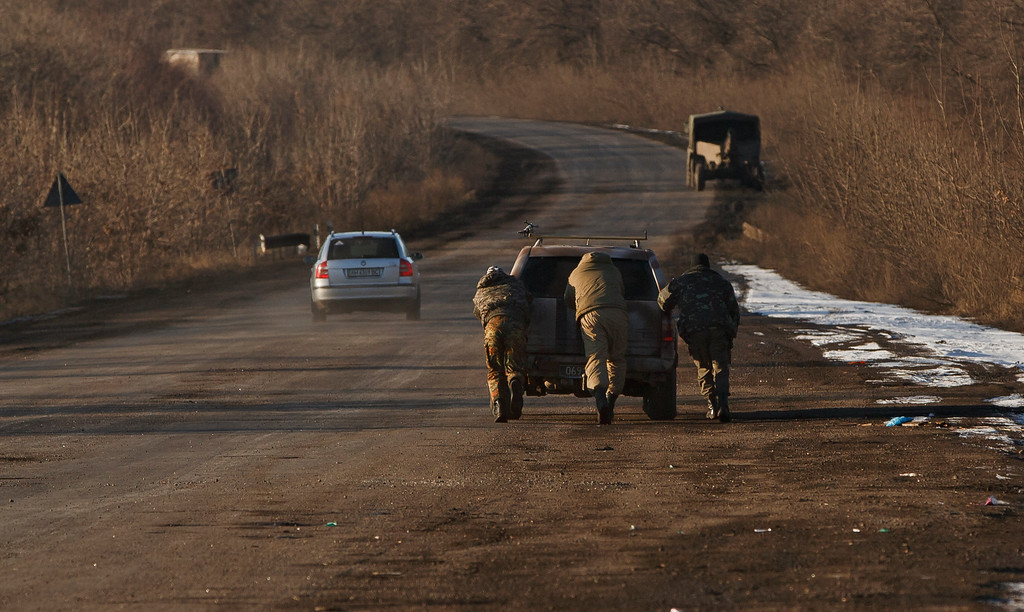 . Ukrainian troops push a car as tehy attempt to start it, outside Artemivsk, Ukraine, while pulling out of Debaltseve, Wednesday, Feb. 18, 2015. After weeks of relentless fighting, the embattled Ukrainian rail hub of Debaltseve fell Wednesday to Russia-backed separatists, who hoisted a flag in triumph over the town. The Ukrainian president confirmed that he had ordered troops to pull out and the rebels reported taking hundreds of soldiers captive.(AP Photo/Vadim Ghirda)