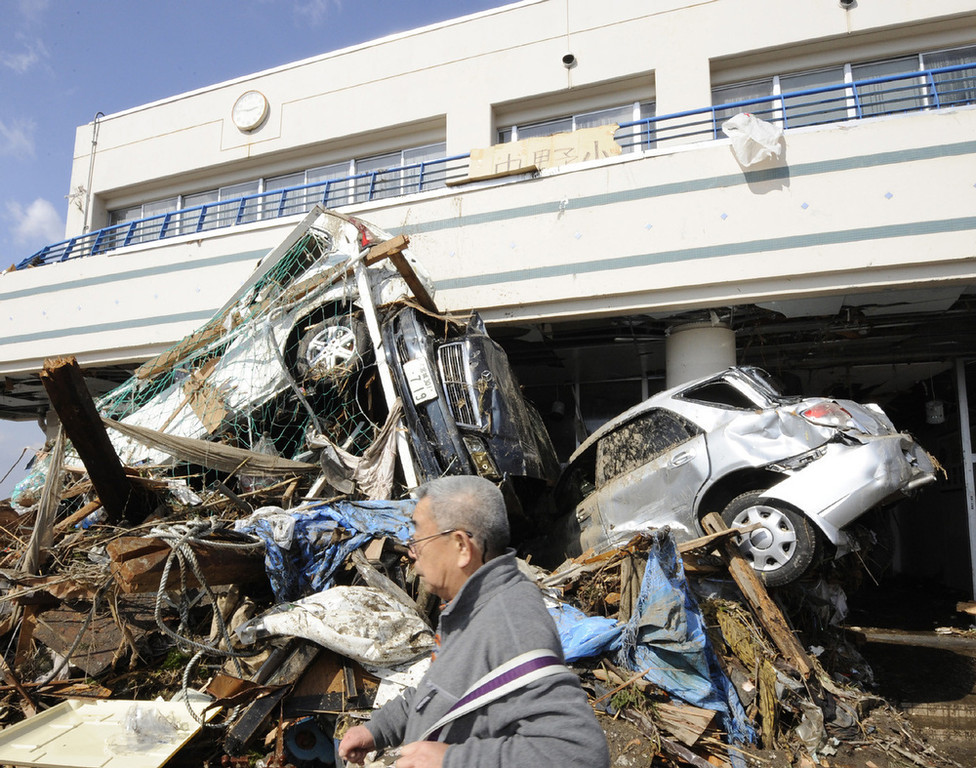 . A man walks past vehicles which were washed away by tsunami into the entrance of an elementary school in Sendai, northern Japan Saturday, March 12, 2011 after Japan\'s biggest recorded earthquake slammed into its eastern coast Friday. (AP Photo/Kyodo News)