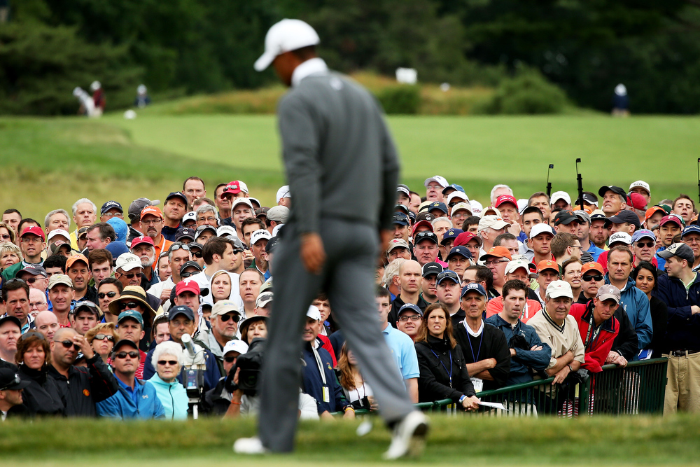 . Tiger Woods of the United States walks across the 18th green as a gallery of patrons look on during a continuation of Round One of the 113th U.S. Open at Merion Golf Club on June 14, 2013 in Ardmore, Pennsylvania.  (Photo by Andrew Redington/Getty Images)