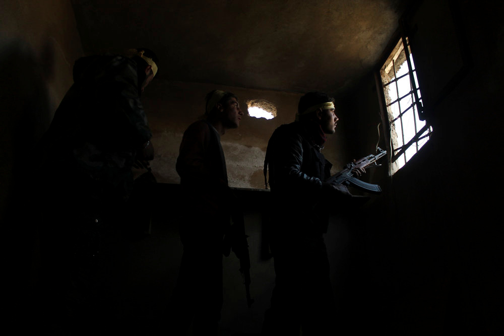 . Members of the Free Syrian Army take up position with their weapons during clashes with forces loyal to Syria\'s President Bashar al-Assad, in the old city of Aleppo March 2, 2013. Picture taken March 2, 2013. REUTERS/Saad Abobrahim