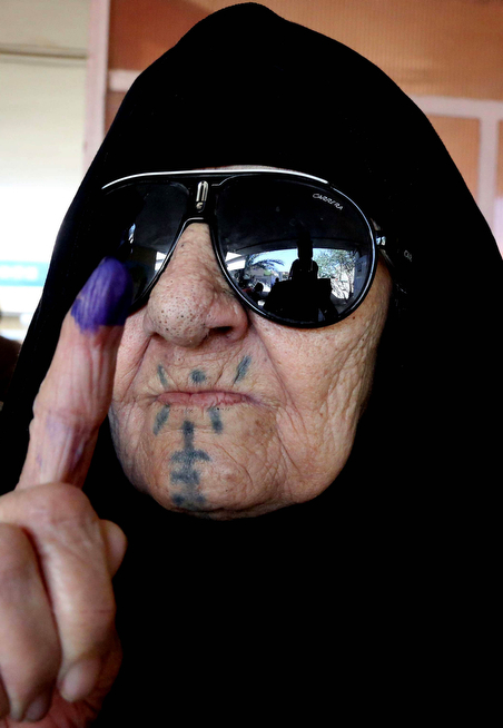 . An Iraqi elderly woman shows her ink-stained finger after casting her vote inside a polling station for parliamentary elections in Baghdad, Iraq, Wednesday, April 30, 2014. Iraq is holding its third parliamentary elections since the U.S.-led invasion that toppled dictator Saddam Hussein.  More than 22 million voters are eligible to cast their ballots to choose 328 lawmakers out of more than 9,000 candidates. (AP Photo/Karim Kadim)