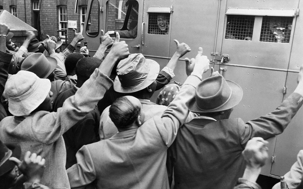 Description of . ANC supporters give the thumb up as a prison van with anti-apartheid militants go to Johannesburg's courthouse, 28 December 1956. 152 anti-apartheid militants, in which Nelson Mandela, are on trial in Johannesburg. (Photo credit should read OFF/AFP/Getty Images)