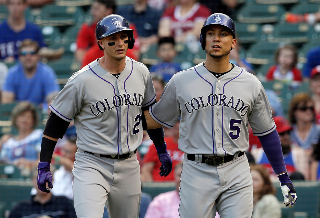 . Colorado Rockies\' Troy Tulowitzki (2) and Carlos Gonzalez (5) congratulate each other after scoring on a Nolan Arenado double in the first inning of a baseball game against the Texas Rangers, Wednesday, May 7, 2014, in Arlington, Texas. (AP Photo/Tony Gutierrez)