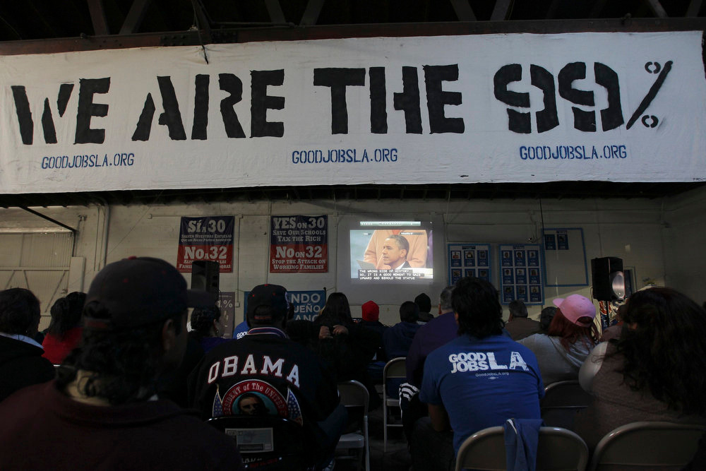 ". Black and Latino watch President Barack Obama approach the podium to take the oath of office as the words of a television announcer referencing Martin Luther King Day appear on the screen, in Gardena, California, January 21, 2013.  President Barack Obama urged Americans on Monday to reject political ""absolutism\"" and partisan rancor as he kicked off his second term with a call for national unity, setting a pragmatic tone for the daunting challenges he faces over the next four years.  REUTERS/David McNew"