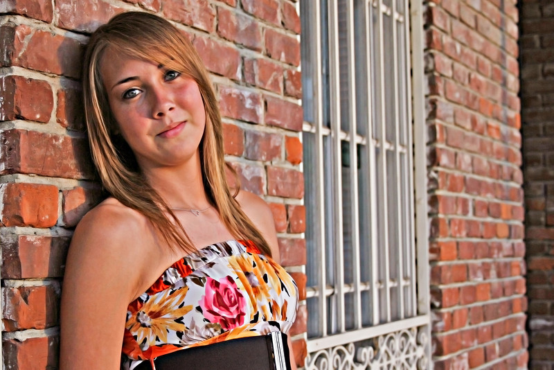 Senior shot! Skin tone and color palette of her clothes matched perfectly against this urban brick backdrop.