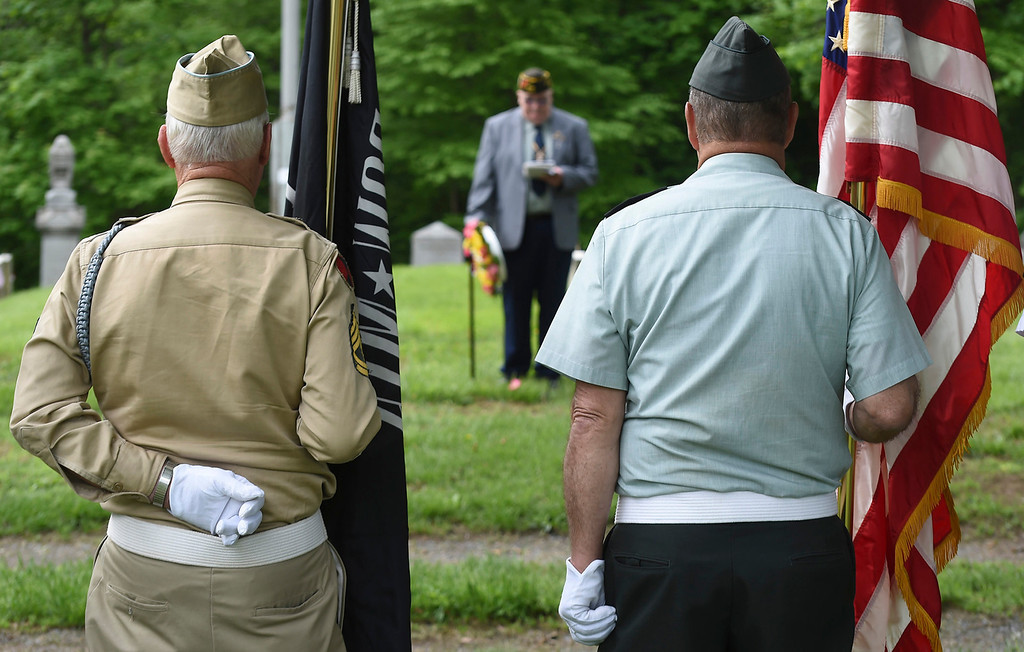 . Kayla Rice/Reformer Local veterans stand with flags while American Legion chaplain E. David Wright speaks during a Memorial Day service in the Prospect Hill cemetery in Brattleboro on Monday morning.