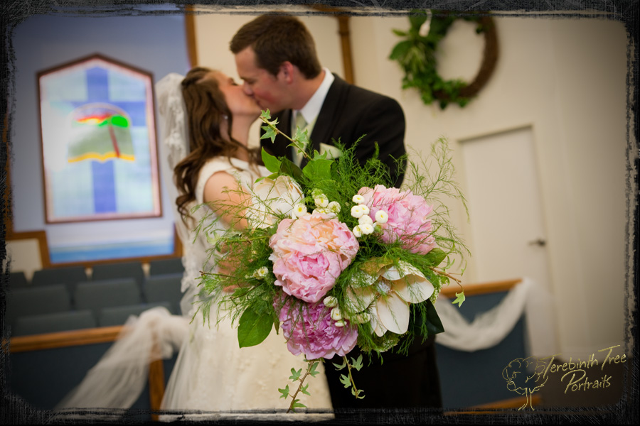 Photo of the bride's bouquet with the couple kissing in the background at our Temecula church