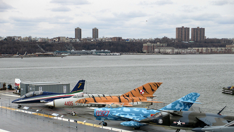 """""""Strange find on U.S. carrier!"""" - Daily Photo - 06/10/13  Two Soviet designed land-based fighters on the flight deck of the USS Intrepid.  The one with the """"tiger"""" is a MiG-21 in the markings of a Polish training squadron and the mottled light blue on dark is a MiG-17.  Picture was taken while walking up to the bridge of the U.S. aircraft carrier."""