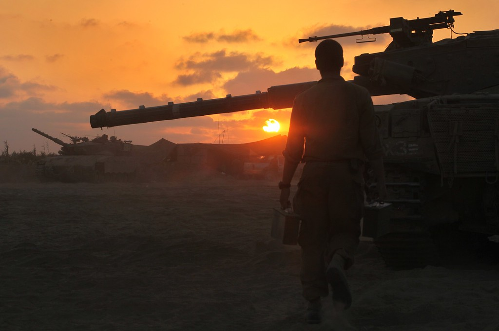 . An Israeli soldier walks past a Merkava tank along the border between Israel and the Hamas-controlled Gaza Strip, on July 30, 2014, after returning from combat in the Palestinian enclave. At least 17 people were killed in an Israeli strike on a packed Gaza market in a deadly raid that came as Israel was observing a four-hour humanitarian lull. AFP PHOTO/GIL  COHEN MAGEN/AFP/Getty Images