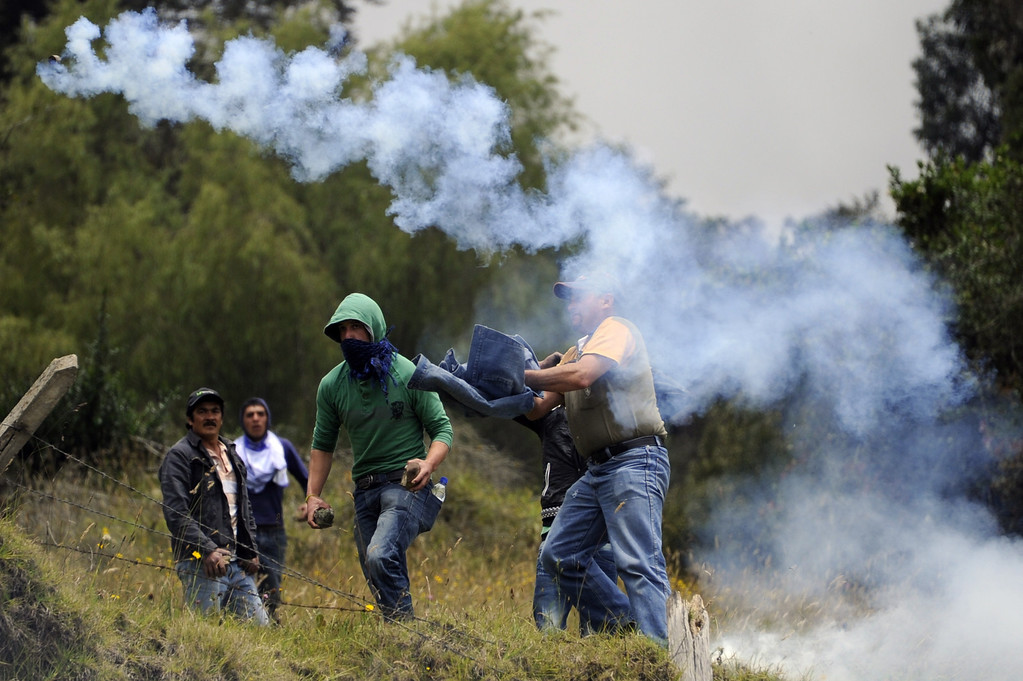 . Stone throwers clash with riot police as Colombian farmers demanding government subsidies and greater access to land block the road in La Calera, Cundinamarca department, on August 23, 2013. A five-day-old farmworkers\' protest in Colombia claimed its first fatality Friday when a man on a motorcycle crashed and died at a roadblock, police said Friday. Since the protests began Monday, farmworkers have closed roads at dozens of points in across the country, blocking the passage of cargo trucks and other vehicles from makeshift camps erected on sides of roads. EITAN ABRAMOVICH/AFP/Getty Images