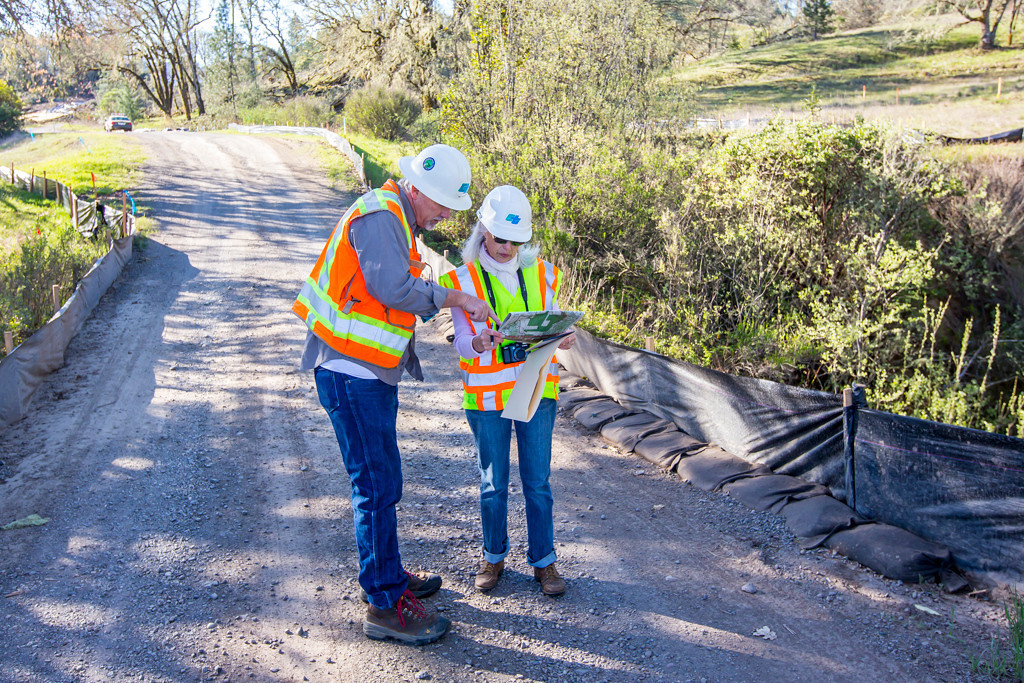 . Private road to local ranches that is now in the footprint of the bypass. This is a one of the many creek crossings. CalTrans worker discusses map with The Willits News Publisher Debbie Clark. Photo by Steve Eberhard.