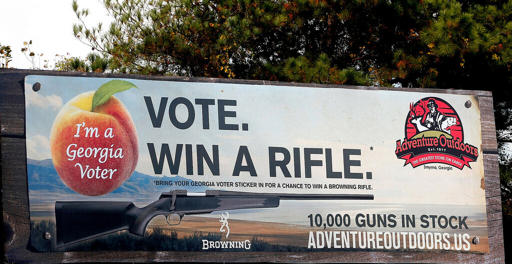 ". One of several billboards of a gun raffle promotion at Adventures Outdoors in Smyrna, Georgia, October 25, 2012. The store has promoted the raffle on billboards as a ""Vote. Win a rifle.\"" but owner Jay Wallace has stated that all Georgia residents were eligible to enter.  REUTERS/Tami Chappell"