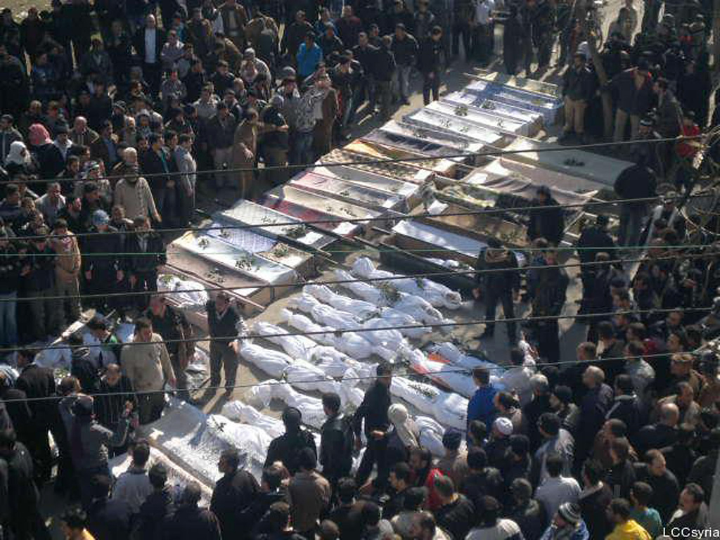 . In this citizen journalism image provided by the Local Coordination Committees in Syria, Syrian mourners gather around the coffins of the victims who were killed early Saturday by the bombardment of mortars and rockets during a mass funeral procession, in Khaldiyeh neighborhood in Homs province, central Syria, on Saturday Feb. 4, 2012. Russia and China vetoed a U.N. Security Council resolution backing calls for Syrian President Bashar Assad to step down, despite international outrage Saturday over a devastating bombardment of the city of Homs by his regime\'s forces. Activists said more than 200 were killed in the bloodiest episode of the nearly 11-month uprising. (AP Photo/Local Coordination Committees in Syria)