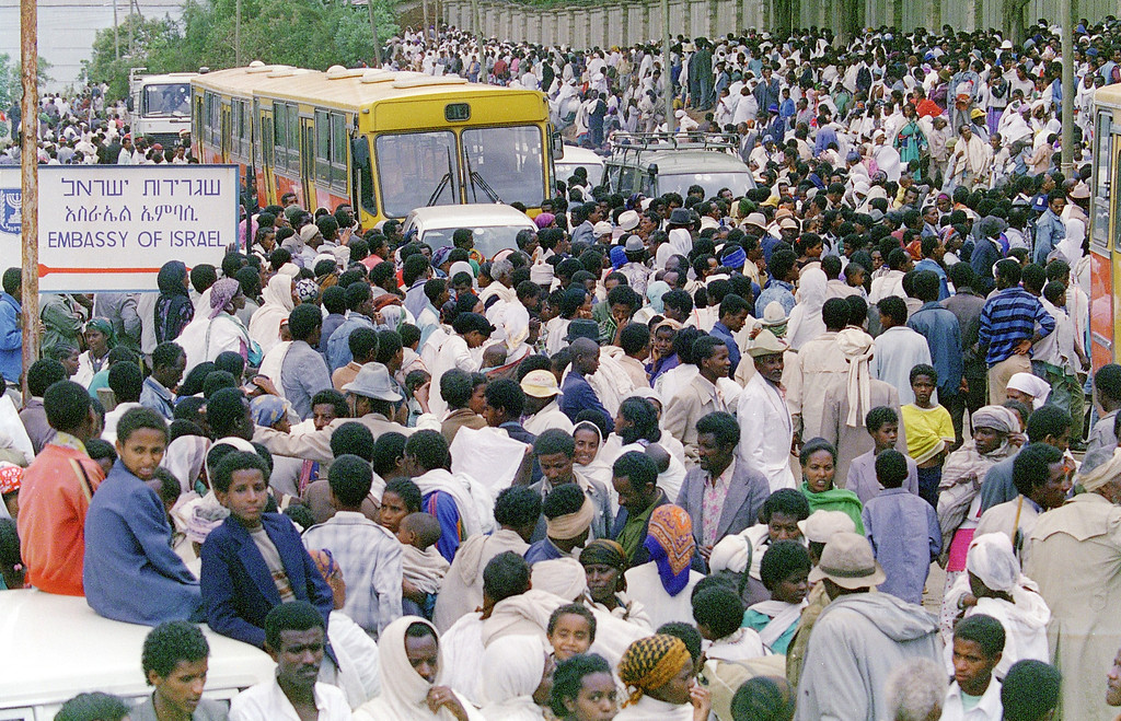 """. ADDIS ABEBA, ETHIOPIA:  Ethiopian Jews, known as \""""Falasha\"""", gather in the thousands outside the Israeli embassy, 24 May 1991, in Addis Ababa, waiting to be bussed to the airport. Israel is planning to take about 1,000 refuges a week out of the country as the civil war continues. JEROME DELAY/AFP/Getty Images"""