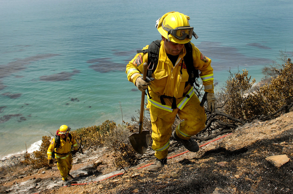 . Cal Fire firefighters Al Spadaro, right, and Dean Marsh climb a hill overlooking the ocean after checking for hot spots, Friday, May 3, 2013. (Michael Owen Baker/Los Angeles Daily News)