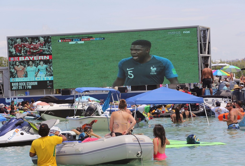 """. Soccer fans cool off in the water while they attending the \""""Ballyhoo Boat Bash\"""" at the Haulover Sandbar in Miami, Sunday, July 15, 2018, as France won its second World Cup title by defeating Croatia in Moscow, Russia. (Carle Juste/Miami Herald via AP)"""