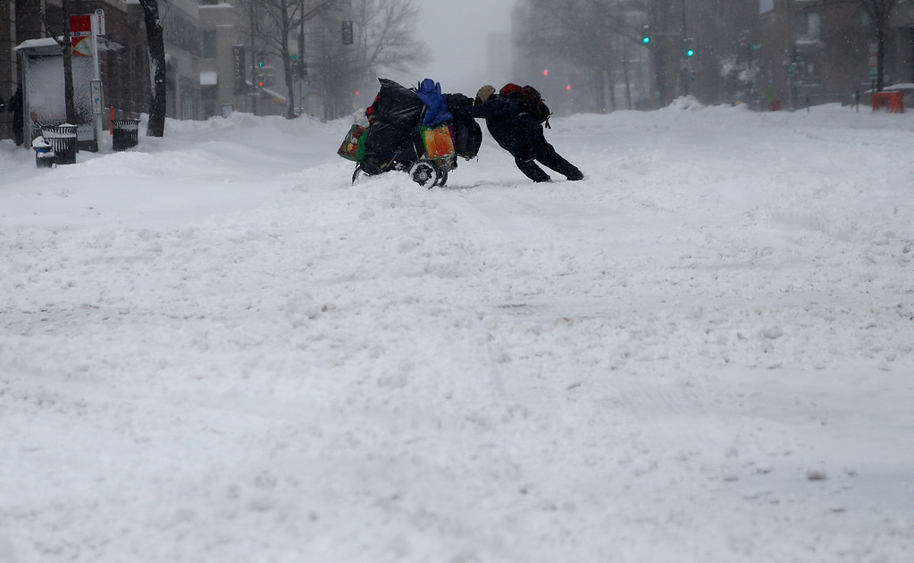 . A homeless man pushes a cart with his belongings across 13th Street in downtown Washington, Saturday, Jan. 23, 2016. Millions of people awoke Saturday to heavy snow outside their doorsteps, strong winds that threatened to increase through the weekend, and largely empty roads as residents from the South to the Northeast heeded warnings to hunker down inside while a mammoth storm barreled across a large swath of the country. (AP Photo/Gerald Herbert)