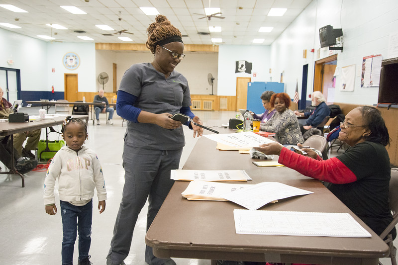 11/05/19  Wesley Bunnell | Staff  Roberta Clements, 3rd L, hands Trena Edney her voting ballot at the VFW 511 voting location early Tuesday afternoon. Edney is accompanied by her 4 year old daughter Sa'har Register.